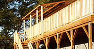 Custom second story cedar deck with covered area and egress stairs.